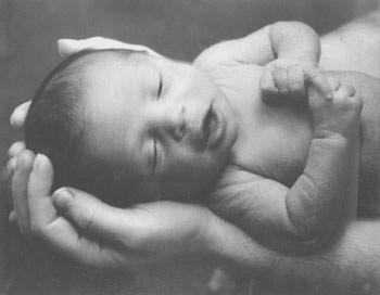 A black and white  picture of a baby being gently held